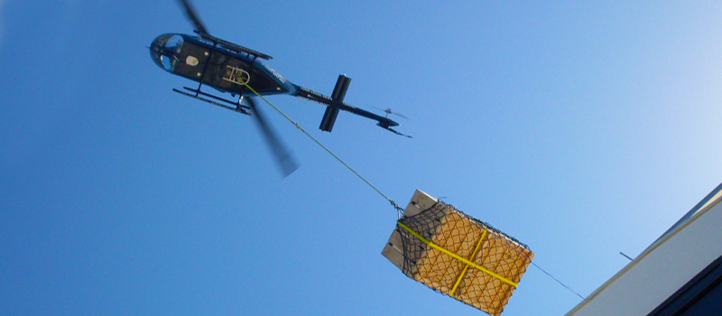 Helicopter using a longline and cargo net to transport a load